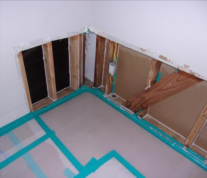 drywall cut showing wood studs and covered with plastic with blue tape